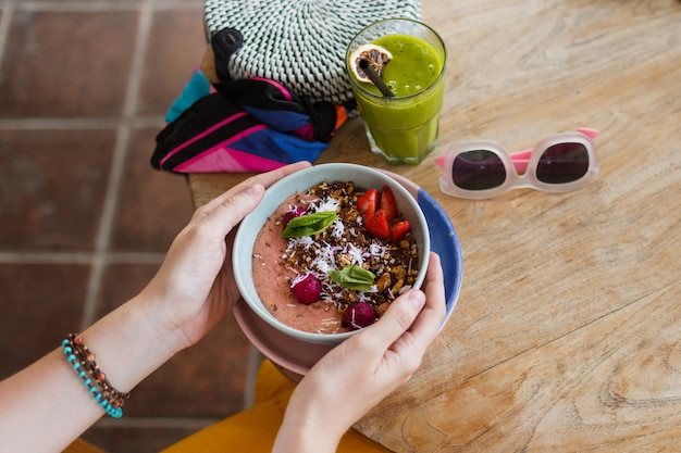 Woman holding smoothie. superfoods bowl topped with chia, granola and avocado.