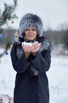 彼女の手のひらに雪を保持している女性