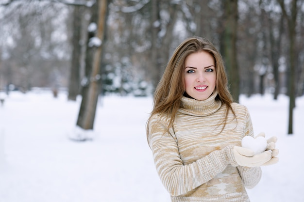 Woman holding a snowball in the shape of a heart