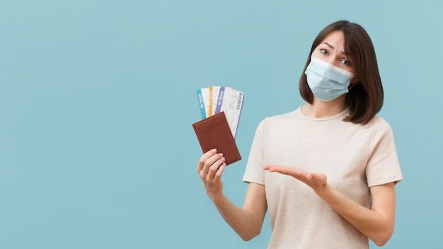 Woman holding some airplane tickets while wearing a medical mask