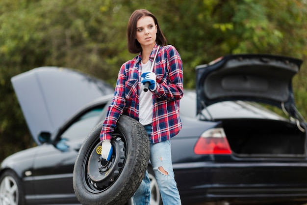 Woman holding spare tire and wrench