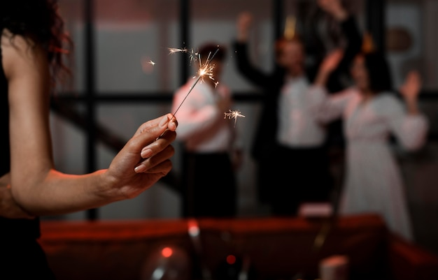 Woman holding sparklers at new year's eve party with copy space