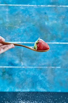 Donna che mantiene un cucchiaio di fragola sulla superficie blu