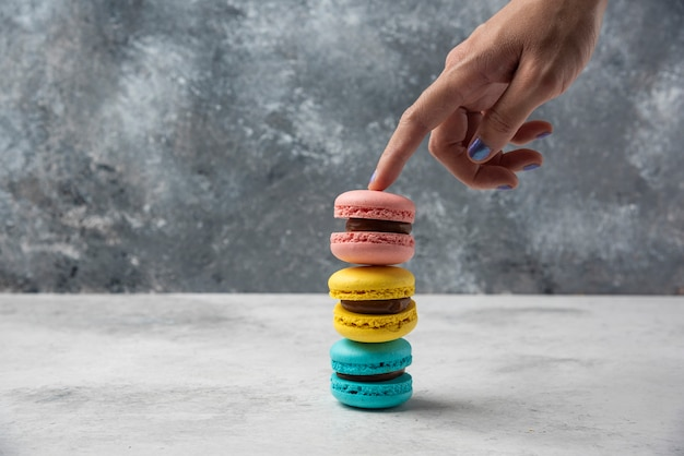 Woman holding stack of macarons on white table.