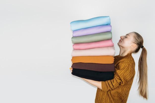 Женщина, держащая стопку пастельных натуральных тканей на белом фоне тканей и одежды