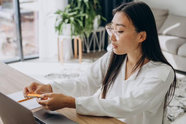 Woman holding stickers to make notes in book while studying