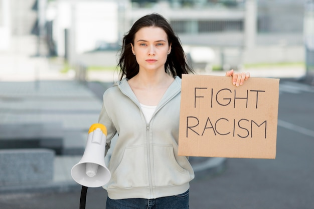 Woman holding stop racism sign and megaphone