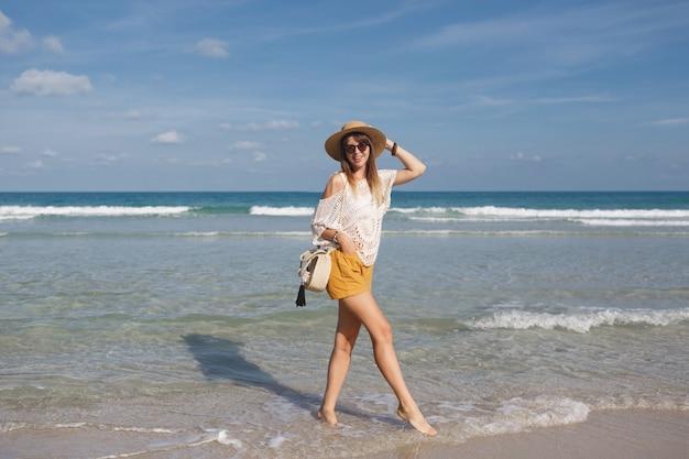 Женщина держит соломенную сумку и гуляет по пляжу