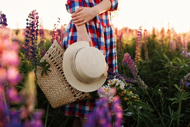 Woman holding straw bag and hat, standing in flower field at sunset.