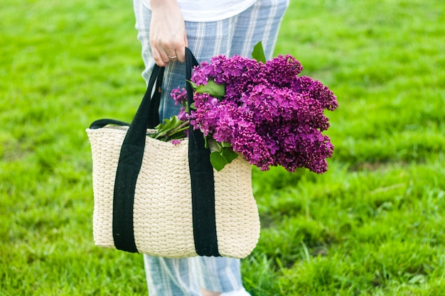 Woman holding straw bag with vivid bunch of lilac flowers