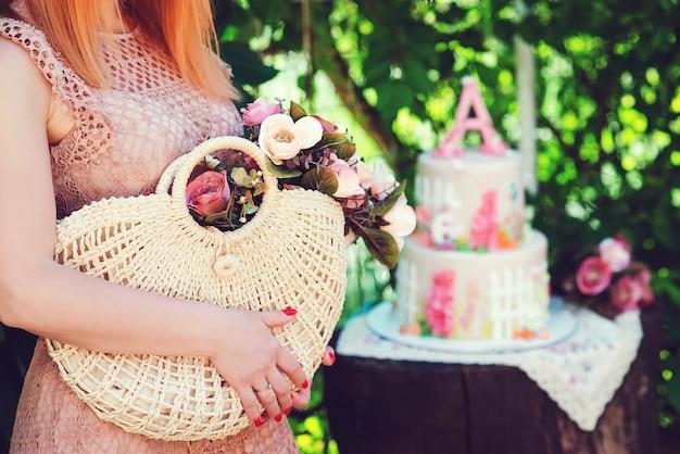 夏の花とわらの籐のバッグを保持している女性。夏のファッション、ライフスタイル、休日のコンセプト。屋外の緑豊かな公園でポーズをとる少女。ファッションの詳細。花と夏のハンドバッグ。
