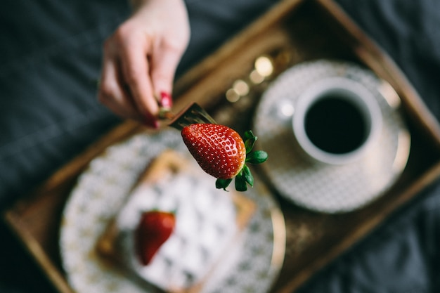 A woman holding a strawberry over a tray