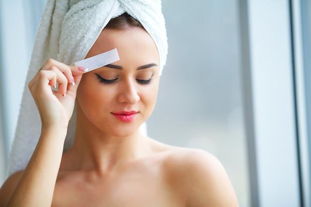 顔の毛を取り除くためにワックスでストライプを保持している女性