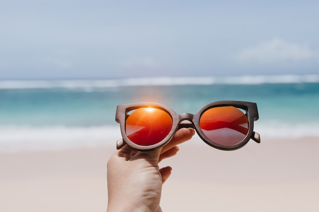 Donna che mantiene gli occhiali da sole estivi alla moda sul mare. foto all'aperto della mano femminile con gli occhiali in spiaggia.