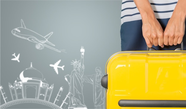 Woman holding suitcase on grey background with sketches