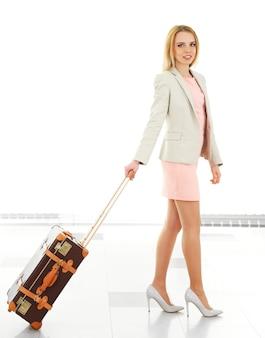 Женщина, держащая чемодан в аэропорту