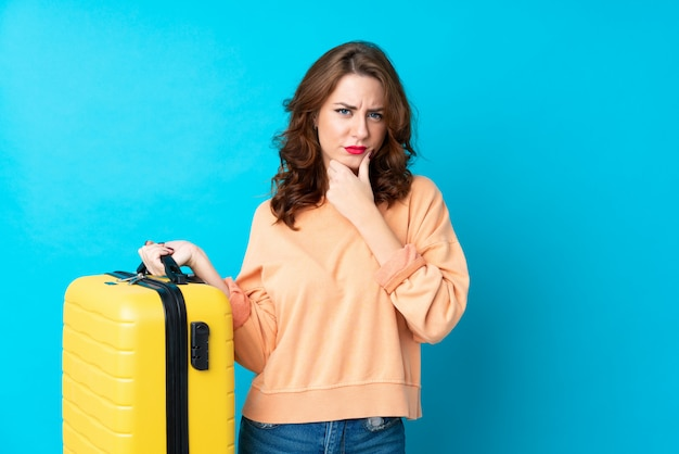 Woman holding a suitcase over isolated wall