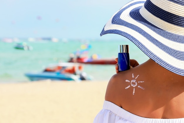 Woman holding the sunblock bottle cream in hand, with sunblock lotion cream applied to her back and draw is the sun.