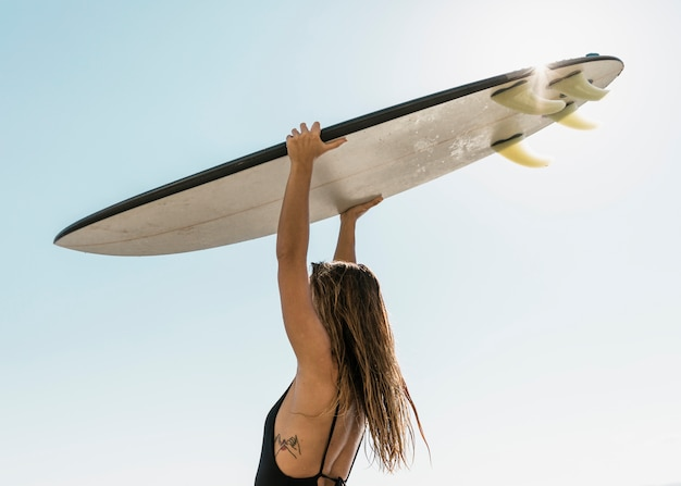 Woman holding surfboard above head