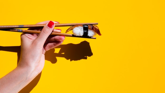 Woman holding a sushi in chopsticks on yellow background