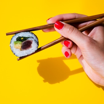 Woman holding a sushi roll in chopsticks on yellow background