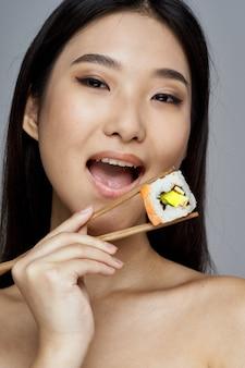 箸で巻き寿司を保持している女性