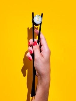 Woman holding a sushi roll in a pair of chopsticks
