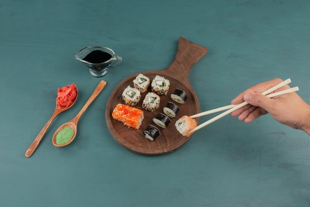 Woman holding sushi roll with chopsticks on blue table with pickled ginger and soy sauce.