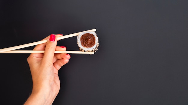 Woman holding a sushi roll with chopsticks on a grey backgrund
