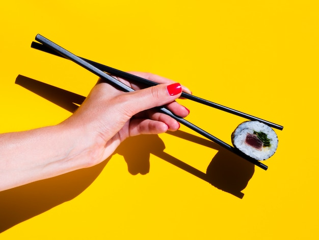 Woman holding a sushi roll on a yellow background