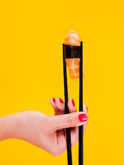 Woman holding a sushi on yellow bacground