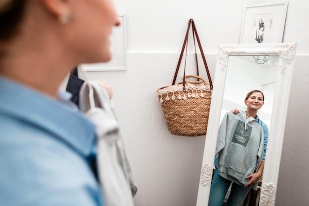 Женщина держит футболку и смотрит в зеркало