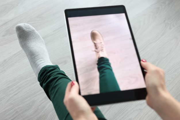 태블릿을 들고 신발 근접 촬영에 노력하는 여자. 온라인 피팅룸 컨셉