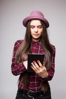 Женщина, держащая планшетный компьютер, изолированные на белой стене. работает на сенсорном экране. вскользь усмехаясь кавказская азиатская женщина.