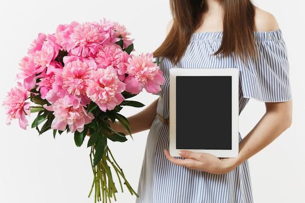 スペースをコピーするために空白の空の画面、白い背景で隔離の美しいピンクの牡丹の花の花束とタブレットコンピューターを保持している女性。ビジネスデリバリーオンラインショッピングのコンセプト。広告エリア