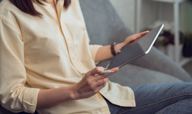 Woman holding a tablet and digital pen on the sofa in house.