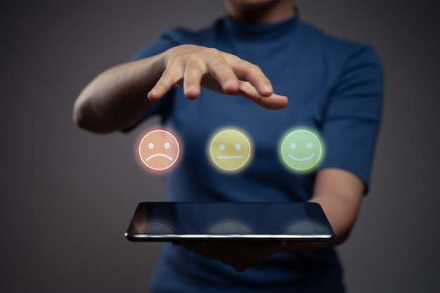 Woman holding tablet and show emoticon hologram effect