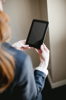 Woman holding tablet or smartphone with hands, black screen