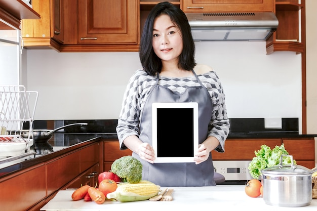 Woman holding tablet standing in kitchen at home