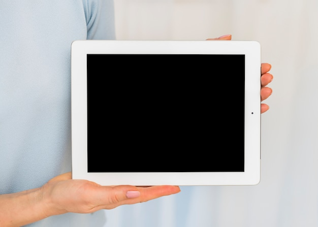 Woman holding tablet with black blank screen