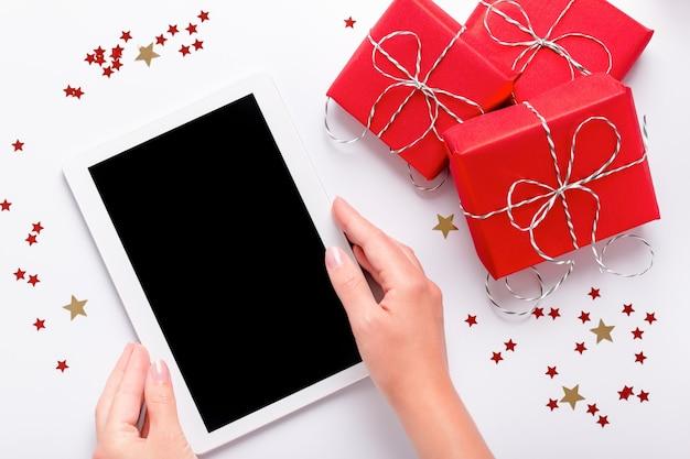 흰색, 위쪽 보기, 평평한 평판에 빨간색 선물 상자와 반짝이는 색종이 조각이 있는 빈 화면이 있는 태블릿을 들고 있는 여성