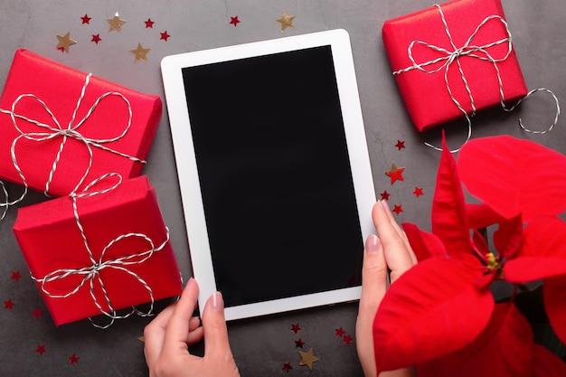 빨간색 선물 상자, 포인세티아 꽃, 초콜릿 별, 크리스마스 조명이 있는 태블릿을 짙은 회색 탁상 위에 들고 있는 여성. 텍스트 공간이 있는 크리스마스 플랫 누워