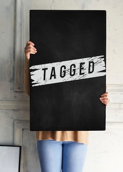Woman holding tagged board