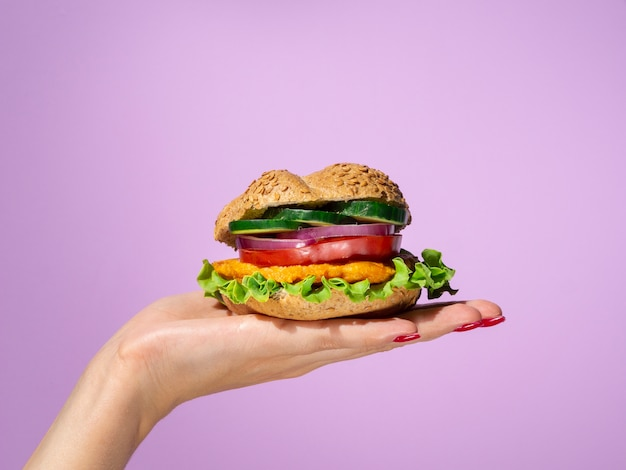Woman holding a tasty burger in her palm