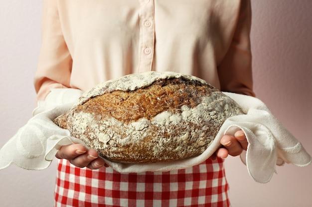 Женщина держит вкусный свежий хлеб, крупным планом