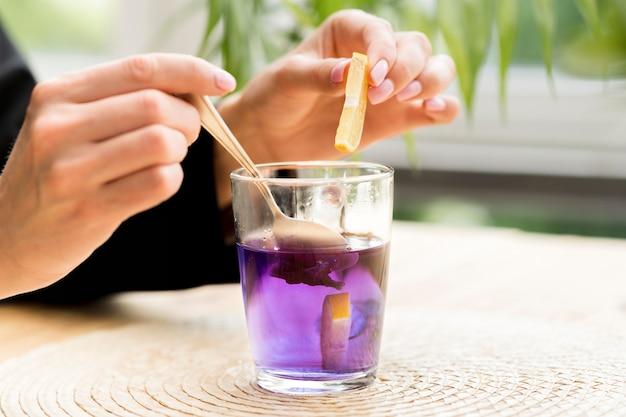 Женщина, держащая чайную ложку и ломтик лимона над фиолетовым чаем