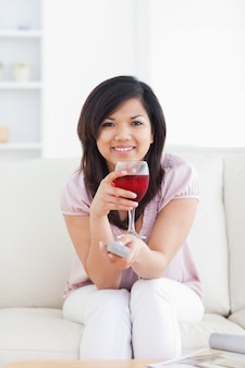 Woman holding a television remote while holding a glass of red wine