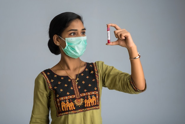 Woman holding a test tube with blood sample for coronavirus or 2019-ncov analyzing.