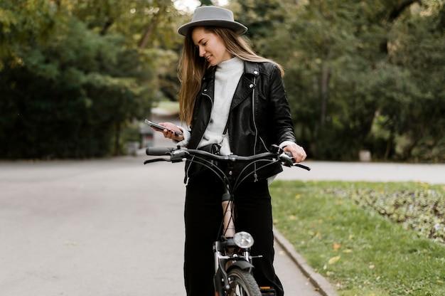 Женщина держит велосипед и использует мобильный телефон