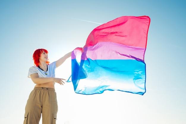 青い空と両性の虹の旗を保持している女性